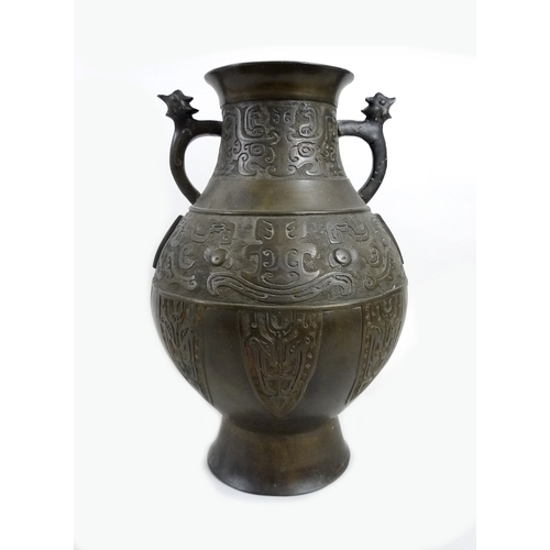 85 - A 19th century Chinese bronze Hu style archaic vase, its main body with two bands of relief decorati...