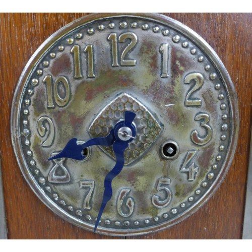119 - An Arts & Crafts style mantle clock, with an oak case, bell to top, pressed and hammered metal dial,...