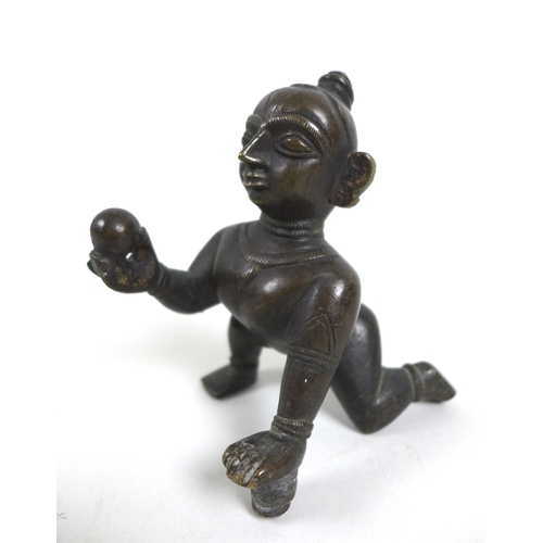 129 - An early 20th century Indian bronze figurine of the infant Krishna, crawling whilst holding a ball o...