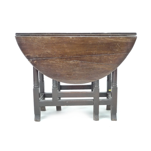 316 - An 18th century oak drop leaf table, circular surface, twin gate leg action, turned supports and bre...