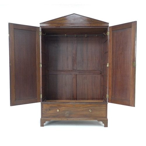 311 - An early 19th century figured mahogany wardrobe, pointed cornice over two doors with brass edging, o...