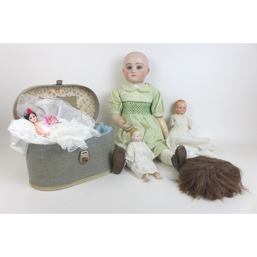 135 - A group of four early 20th century and later dolls, comprising an 'S and C' bisque headed doll, with...