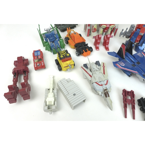 141 - A group of nine 1980s Transformers toy action figures, including Hot-Rod, two Metroplex figures, and...