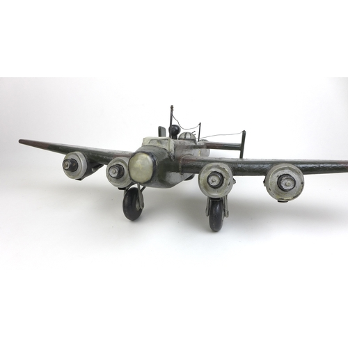 139 - Two circa WW2 era wooden toys, a circa WW2 home made wooden Halifax bomber, with hand painted camouf...