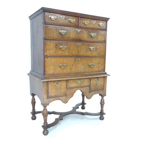 331 - An early Georgian chest on stand, an arrangement of drawers with brass plate handles, the base secti...