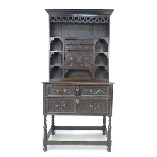 318 - An 18th century and later oak chip carved dresser of small proportions, with a series of drawers and...