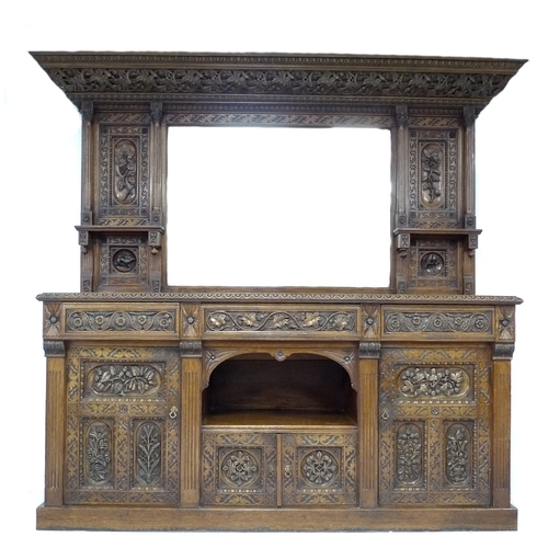 285 - An Arts and Crafts oak carved sideboard by Edward Bowman, with mirrored gallery back, three frieze d...
