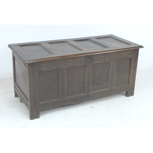317 - An 18th century oak chest, lift lid with loop hinges, four panel front below a carved frieze, on sti...