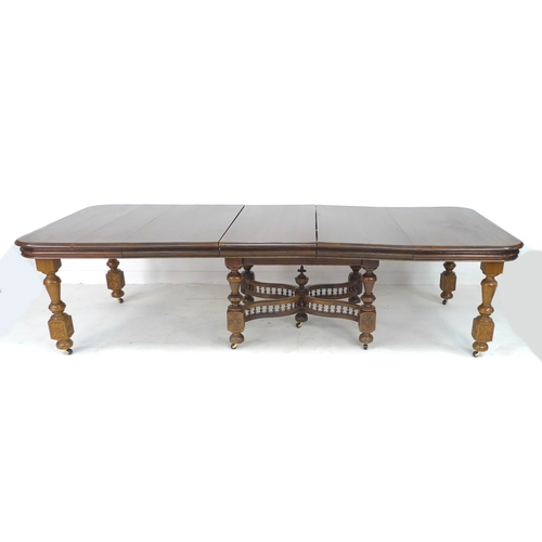 332 - A French oak dining table, the rectangular surface with rounded corners and moulded edges, three add...