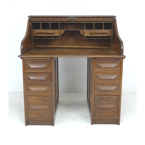 280 - An oak roll top desk, circa 1940, made by Cutler, twin pedestals each with four drawers, fitted inte...