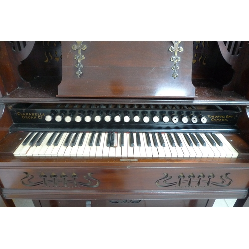 335 - A late 19th century Canadian Clarabella harmonium, with mahogany case, a square form stained glass m...