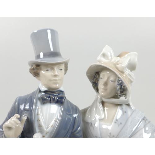 31 - A Royal Copenhagen porcelain figural group, modelled as a Victorian lady and gentleman, model 1593, ...