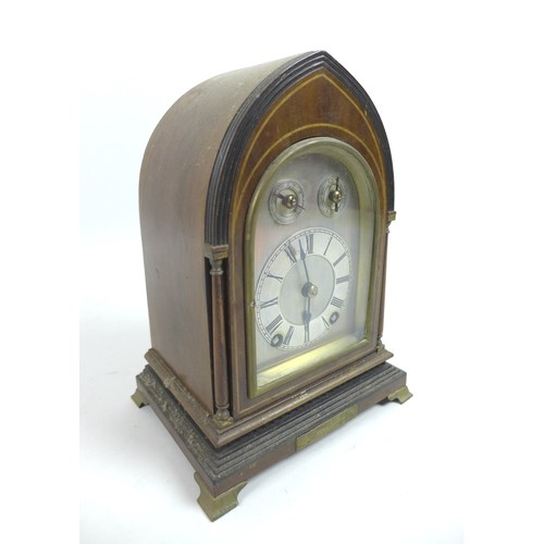 33 - An Edwardian mahogany & inlaid mantel clock, of lancet form, the silvered dial with black Roman nume...