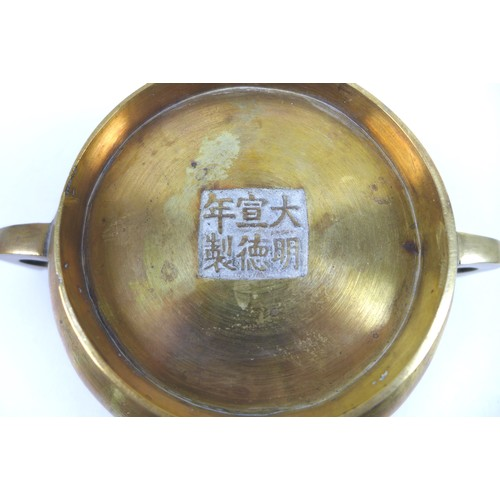 2 - A Chinese polished bronze censor, of twin handled squat circular form, raised on a high foot rim, ca...