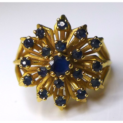 161 - A 14ct gold and sapphire dress ring, the central round cut stone surrounded by eighteen smaller ston...
