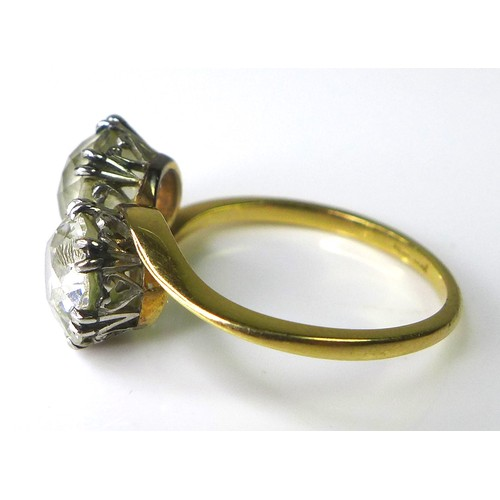 199 - A crossover two diamond ring, composed of one Old European cut and one more modern cut diamond, the ...