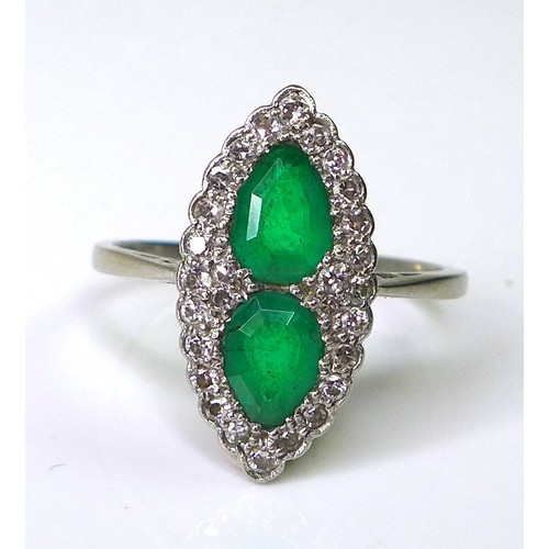 182 - An Art Deco emerald, diamond and platinum dress ring, of scalloped marquise form, with two pear cut ...