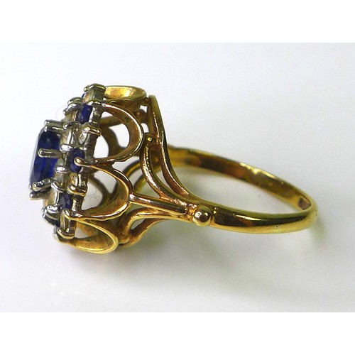 158 - A sapphire, paste and 9ct gold dress ring, the central oval cut sapphire of approximately 5mm by 7mm...