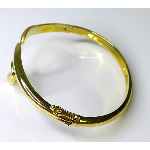 168 - A 14ct gold bangle of sinuous design, with hinged clasp, 19.3g....