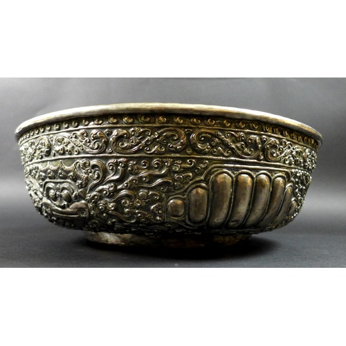 10 - A late 19th century Thai silver large bowl, repousse decorated in relief with three face masks and t...