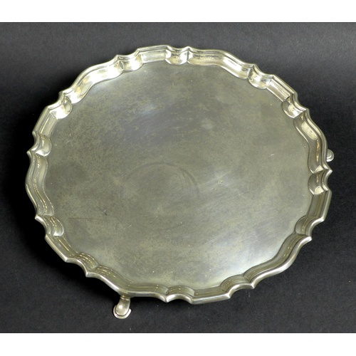 56 - A George V silver tray, of circular form with Chippendale pie crust edge, raised on three feet, reta...