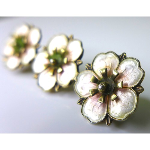 157 - A silver and enamel brooch of apple blossom design, 1930s, composed of three blossoms in a row, enam...