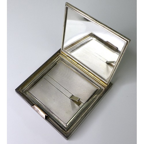 122 - An Art Deco silver compact mirror, of square form with engraved geometric decoration and engine turn...