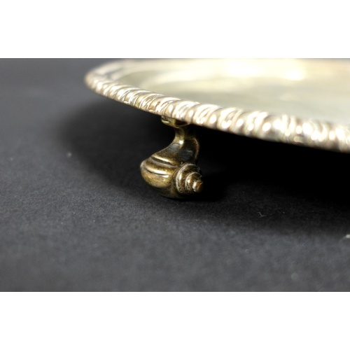 54 - A George III small silver tray, of octagonal form with reeded rim, three scroll feet, maker's mark '...