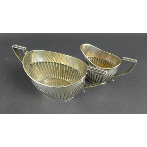 48 - An Edwardian silver sugar bowl, 20 by 9.5 by 10.3cm high, and a silver milk jug, 12.6 by 6.4 by 8.9c...