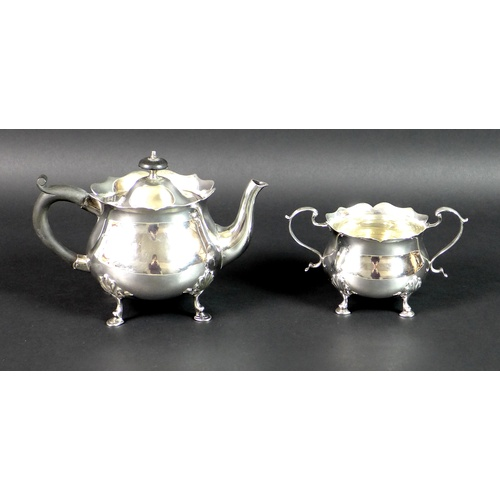 49 - An Edward VII silver teapot and sugar bowl, of bombe form with scalloped rims, raised on four shell ...