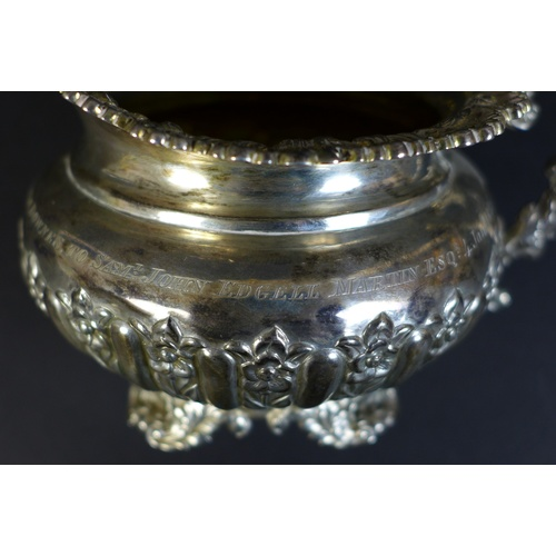 33 - A George IV silver milk jug, with profuse repousse and applied decoration, raised on four shell and ...