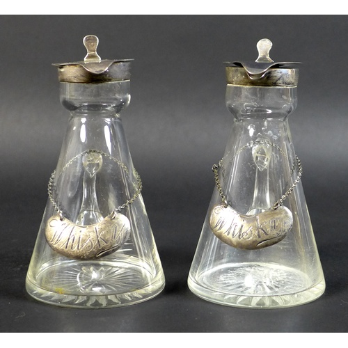 42 - A pair of Edwardian clear glass and silver mounted noggin flasks, each of tapering form with mounted...