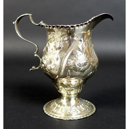 51 - A George III silver cream jug, decorated with chased and repousse flowers, with rococo cartouche, on...