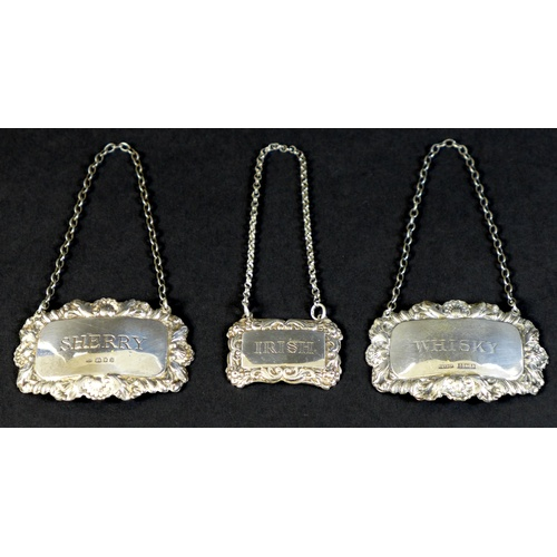21 - A group of three silver decanter labels, each with cast foliate decorative borders, comprising a sma...