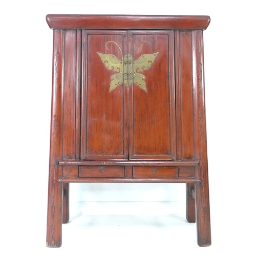 209 - A modern Chinese style cabinet, of tapering form with red lacquered finish, brass butterfly shaped l...