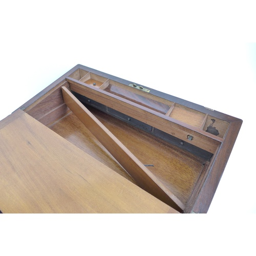 99 - A large Victorian mahogany writing slope, with a secret bank of three drawers, each with hand writte...