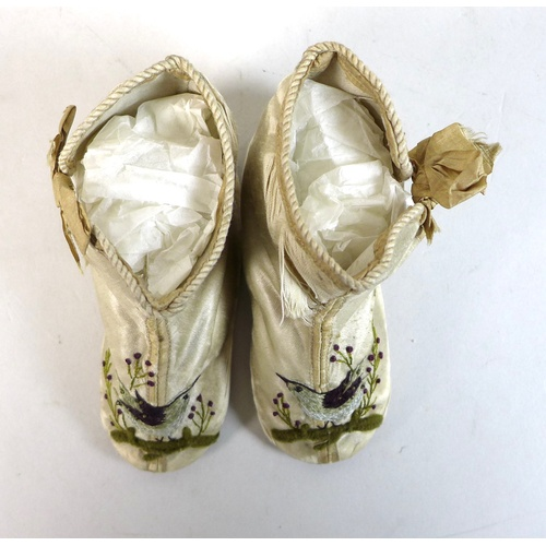 106 - A pair of Edwardian baby's boots, circa 1900, leather soles and cream silk, with two bows to the sid...