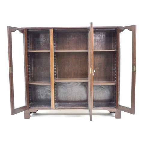 229 - A mid 20th century mahogany glazed bookcase, with three glazed doors each enclosing two adjustable s...