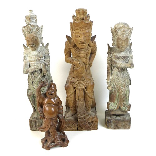 26 - A group of four wooden carvings, comprising a Chinese carving of a man holding a flower aloft, 20cm,...