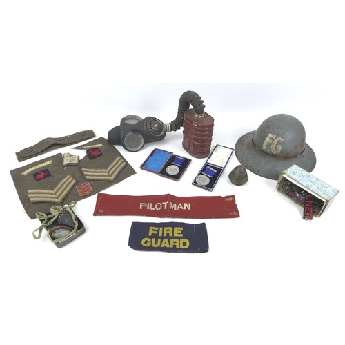 95 - A WWII gas mask, a Fire Guard helmet and arm band, three cap badges, Royal Warwickshire, Northampton...