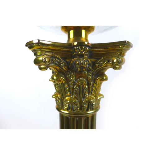 74 - A Victorian brass paraffin lamps, both with clear glass reservoirs on a Corinthian columns and squar...