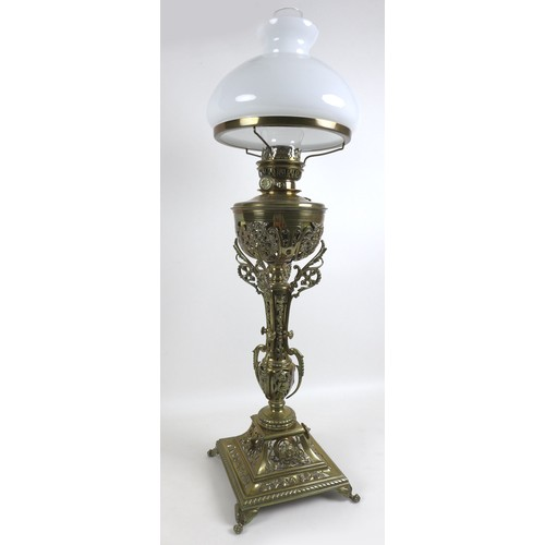 73 - A Victorian brass paraffin lamp, with brass reservoir on a cast floral column, clear glass chimney a...