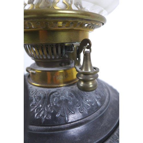 75 - A Victorian cast metal paraffin lamp, with clear glass reservoir on a cast base, decorated in relief...