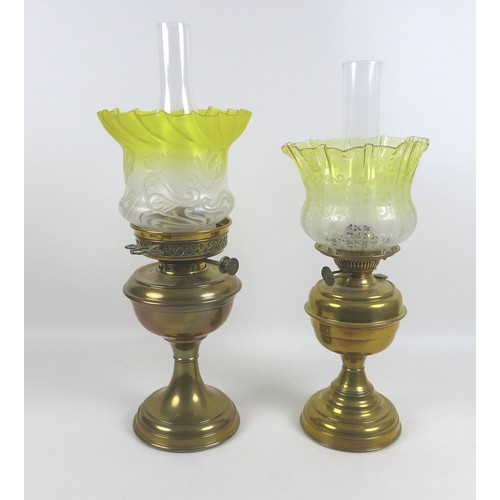 71 - Two Victorian brass paraffin lamps, each with a brass reservoir on circular base, clear glass chimne...