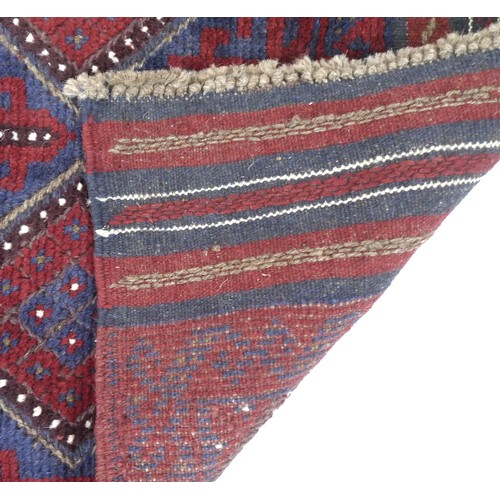 235 - A Meshwari runner, with dark red and blue ground, twelve diamond medallions to the field accented by...