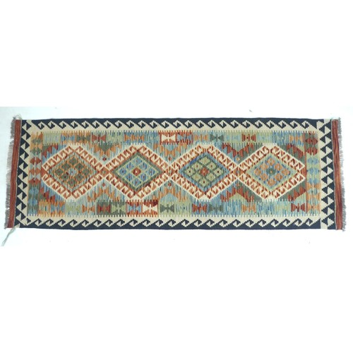 191 - A vegetable dyed wool Choli Kelim runner, with four large diamond medallions to the field and geomet...