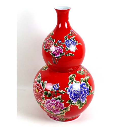 23 - A large modern Chinese porcelain double gourd vase, with printed floral decoration against a red gro...