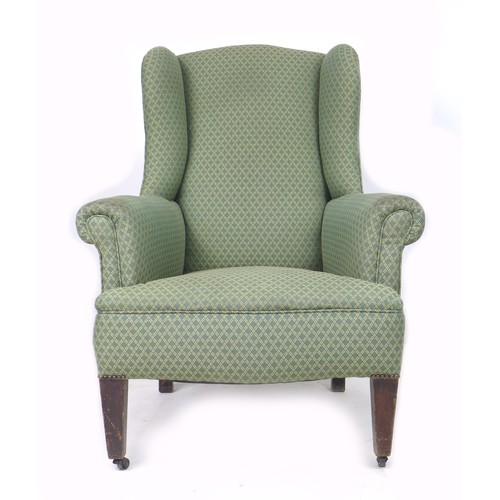 191 - A mid 20th century wing back armchair, with tapered legs, upholstered in green diamond patterned fab...