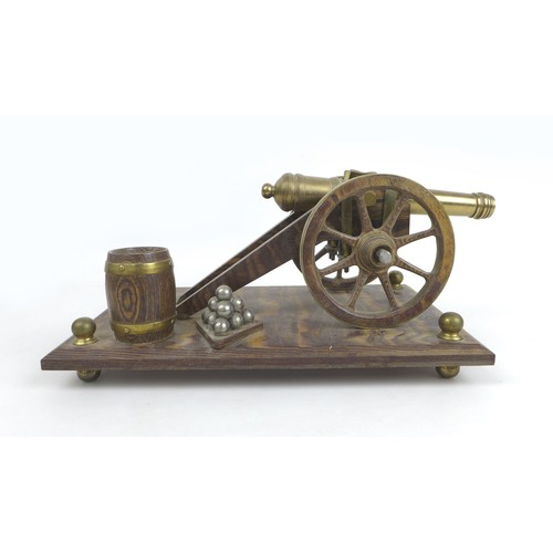 63 - A mid 20th century brass and oak model canon on stand, overall 31 by 17 by 13cm high....
