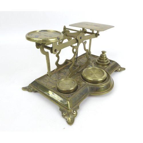30 - A set of Victorian brass postal scales, with six weights, with relief foliate decoration to its base...